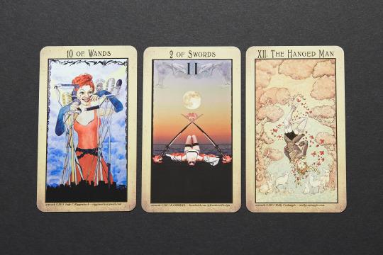 Three tarot cards: 10 of Wands, 2 of Swords, The Hanged Man
